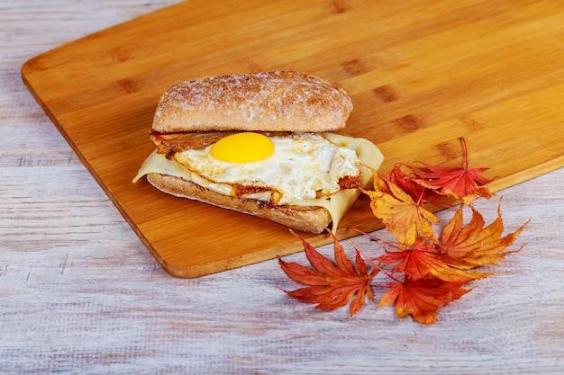 Sandwich mit speck und hühnerei auf hölzernem.
