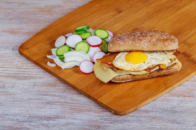 Sandwich mit speck und hühnerei mit rettich- und zwiebelgurken