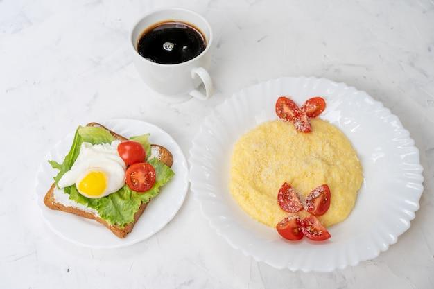 Sandwich mit spiegeleisalat und -tomate auf plattenweiß mit copyspace