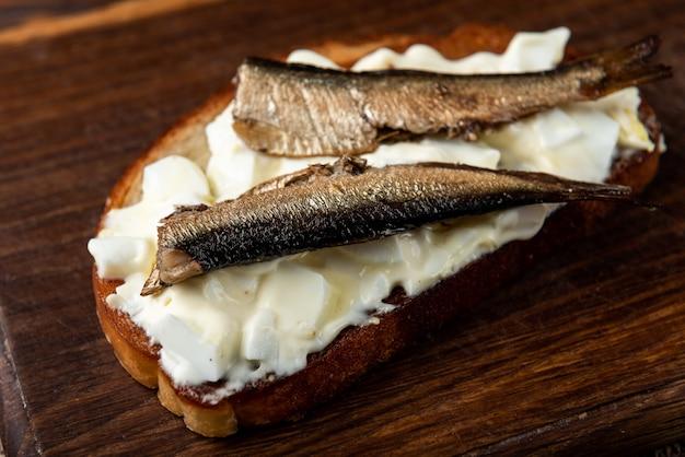 Sandwich mit sprotten, eiern und mayonnaise auf holztisch.