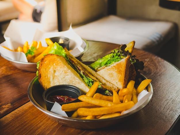 Sandwich mit thunfischgemüse, tomate, käse und goldenen pommes-frites.