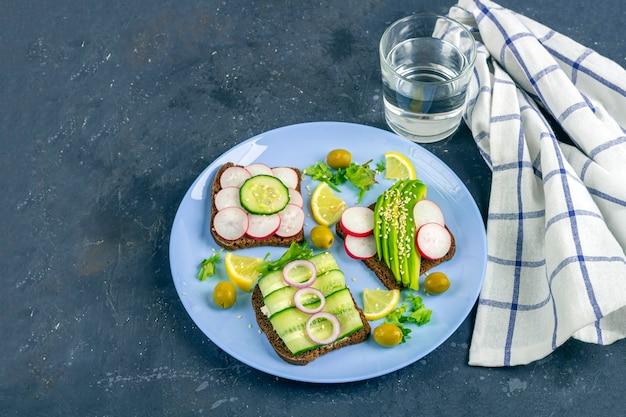 Sandwich mit verschiedenen belägen avocado, gurke, rettich auf teller mit einem glas wasser auf dunklem hintergrund