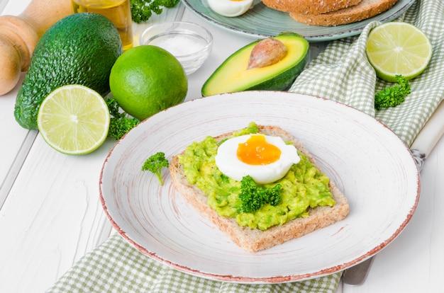 Sandwich mit vollkornbrot, zerdrückter avocado und gekochten eiern auf der platte.