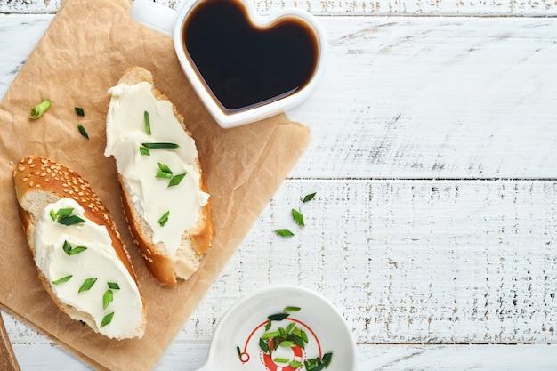 Sandwich mit weichkäse mit frühlingszwiebeln und brot auf altem weißem holzhintergrund. einfaches frühstück mit ricotta-sandwich und kaffee. draufsichtkopierraum für text.