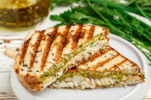 Sandwich mit weißem fisch und grüner pestosoße