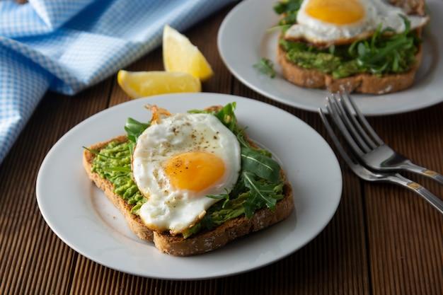 Sandwich- oder brottoast mit avocado und einem spiegelei. gesundes essen.