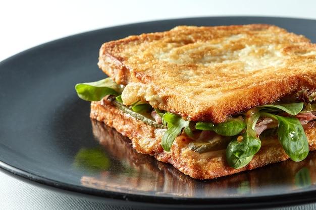 Sandwich panini auf dem grill auf dem schwarzen teller