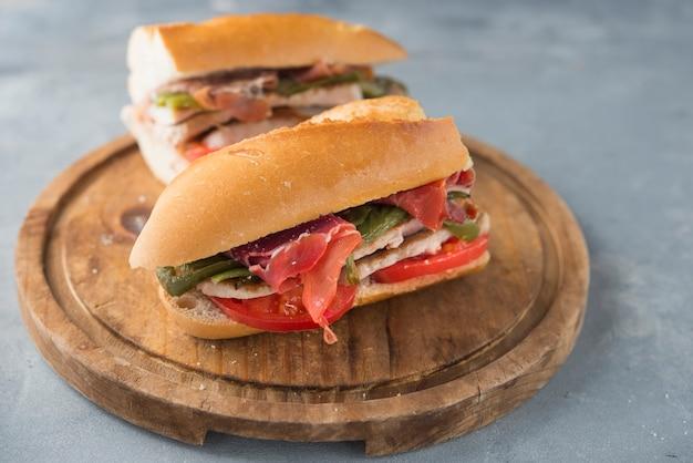 Sandwich serranito typisch für andalusien mit schinken, gren pfeffer und gegrillter schweinelende