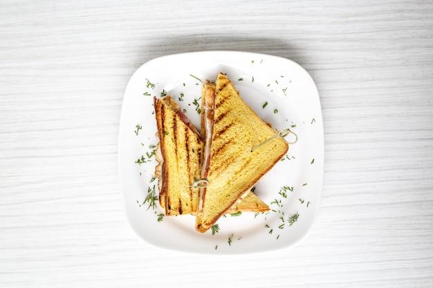 Sandwich toast gegrillt mit käse, speck und salat auf weißem holztisch, oberfläche