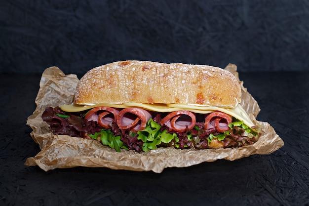 Sandwich von knusprigem ciabatta mit schinken-, käse- und salatblättern.