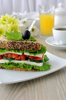 Sandwichbrot mit müsli, käse, tomate und gurke