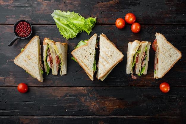 Sandwichbrot tomate, salat und gelber käse, auf altem holztisch, draufsicht