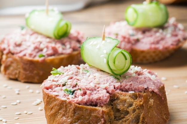 Sandwiche mit hühnerpastete und gurke auf holztisch.
