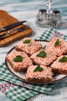 Sandwiche mit krabbenstöcken und -karotten auf einer platte auf einem blauen hintergrund