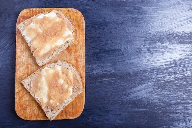 Sandwiche mit pollockrogen auf einem hölzernen küchenbrett gegen schwarzen hintergrund, draufsicht