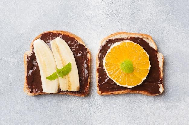 Sandwiche mit schokoladenmasse und verschiedenen früchten auf einer grauen tabelle.