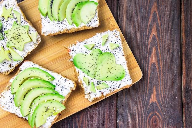 Sandwiche vom brot mit scheiben, sternen, herzen von der avocado und vom quark auf hölzernem hintergrund.