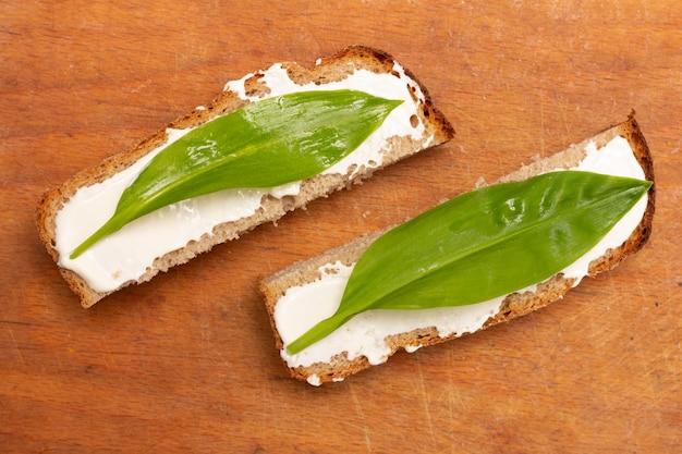 Sandwiche von den scheiben brot mit majonäse- und bärlauchblättern, abschluss der draufsicht oben