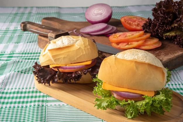 Sandwiches auf einem holzteller auf einer karierten tischdecke