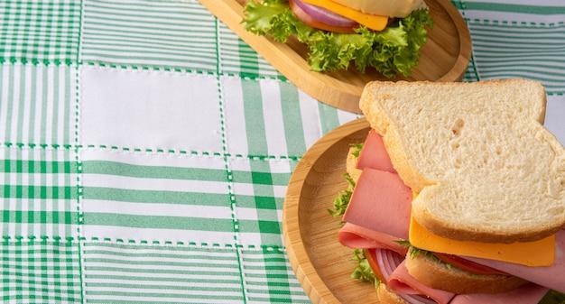 Sandwiches auf einem holzteller auf grün-weiß karierter tischdecke