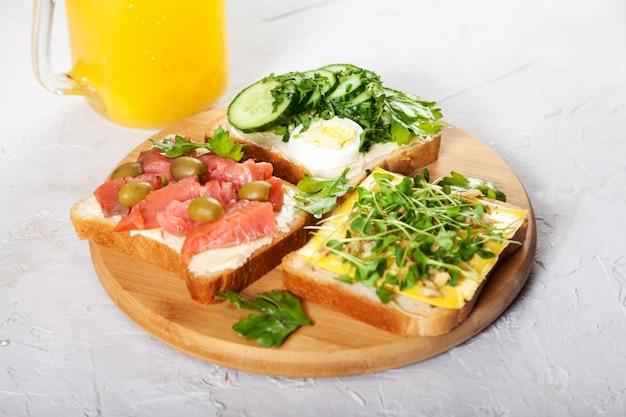 Sandwiches auf toastbrot mit lachs, ei, kräutern und gemüse auf einem holzbrett und orangensaft