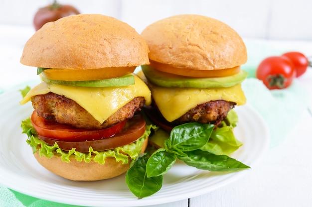 Sandwiches (burger) mit gelben und schwarzen tomaten, saftigem schnitzel, avocado auf einem teller auf weißem holz.