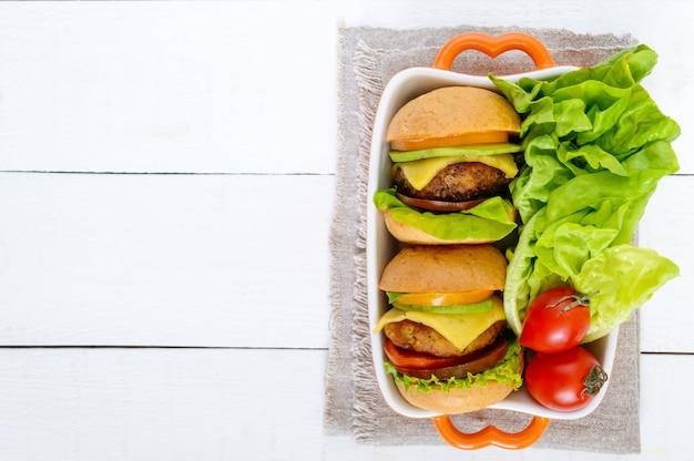 Sandwiches (burger) mit gelben und schwarzen tomaten, saftigem schnitzel, avocado auf weißem holz.
