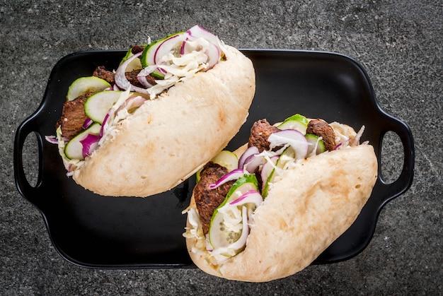 Sandwiches. fast food. asiatische bao brötchen des traditionellen chinesen mit dem fleisch, das schweinefleisch, rindfleisch, frischgemüse und scharfer soße anfüllt. auf einem dunklen steintisch. ansicht von oben