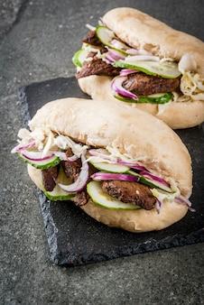 Sandwiches. fast food. asiatische bao brötchen des traditionellen chinesen mit dem fleisch, das schweinefleisch, rindfleisch, frischgemüse und scharfer soße anfüllt. auf einem dunklen steintisch.