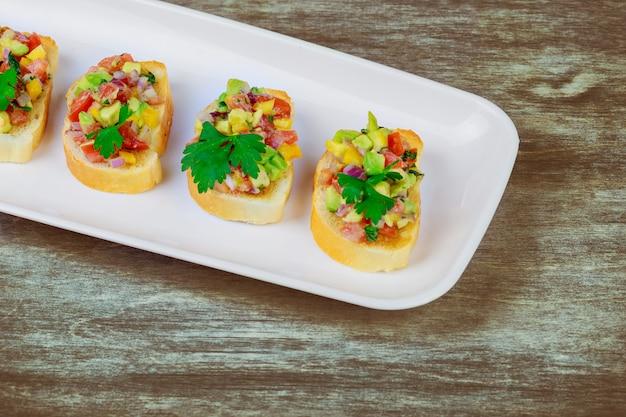 Sandwiches gesundes schnellimbiß mit avocado und lachsen auf frühlingszwiebeln und brot und tomaten.