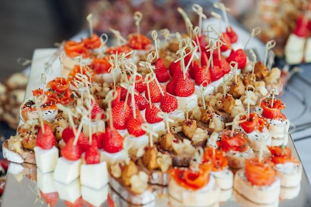 Sandwiches, häppchen und kuchen auf dem festlichen tisch. eine große auswahl an snacks. einschließlich für veganer