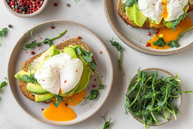 Sandwiches mit avocado, pochiertem ei, sprossen und käse für ein gesundes frühstück auf weiß