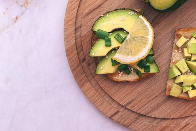 Sandwiches mit avocado, tomaten und kräutern auf einem hölzernen hintergrund auf dem tisch. konzept von gesunder ernährung und vegetarismus, das richtige frühstück für eine gute verdauung.