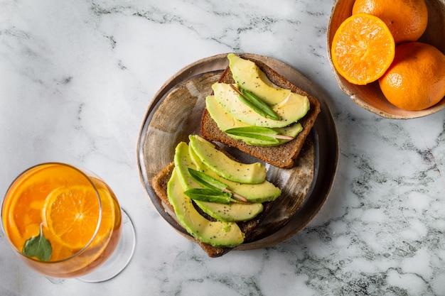Sandwiches mit avocado und cocktail auf marmorhintergrund