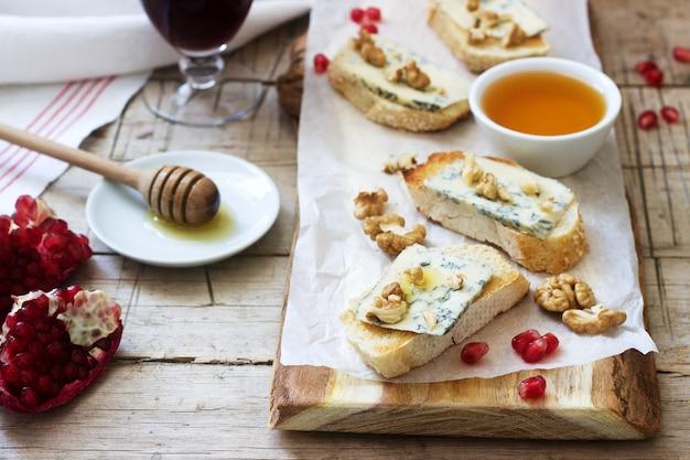 Sandwiches mit blauschimmelkäse, granatapfel, honig und nüssen, serviert mit rotwein. rustikaler stil.