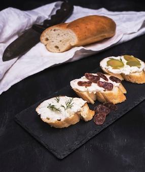 Sandwiches mit cremeweißkäse, wurst, oliven und dill