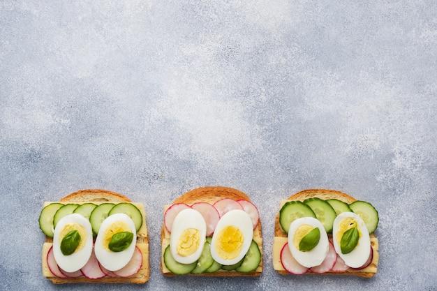 Sandwiches mit eierkäse, frischer gurke und rettich.