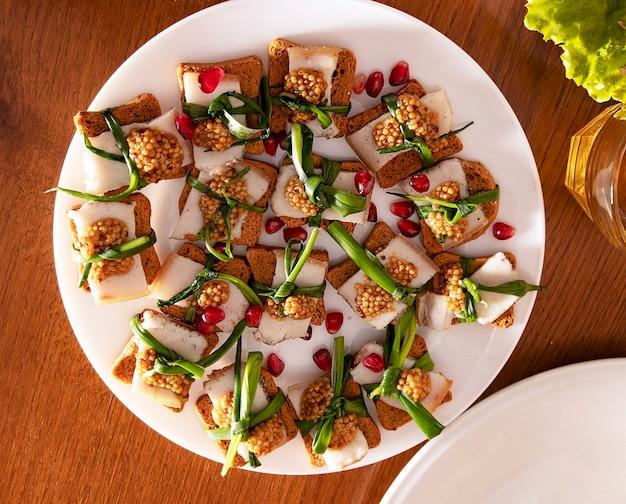 Sandwiches mit fetten speck-frühlingszwiebeln und senf- und granatapfelkörnern auf einem weißen teller