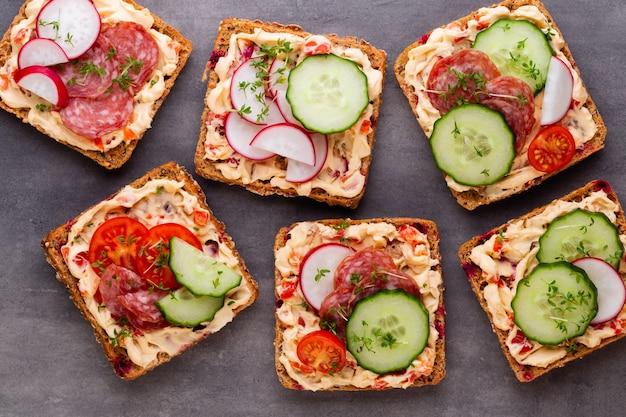 Sandwiches mit frischkäse, gemüse und salami. sandwiches mit gurke, rettich, tomaten, salami auf grauem hintergrund, draufsicht. flach liegen.