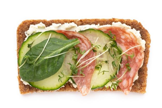 Sandwiches mit frischkäse, gemüse und salami. sandwiches mit gurke, rettich, tomaten, salami auf weißem hintergrund, draufsicht. flach liegen.
