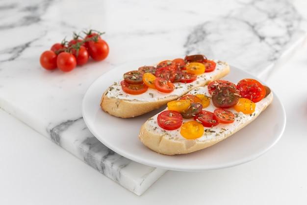 Sandwiches mit frischkäse und tomaten auf teller