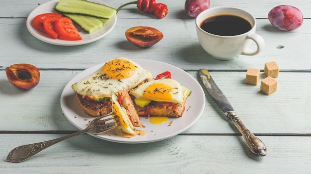 Sandwiches mit gemüse und spiegelei auf weißem teller kaffee und einigen früchten über holz