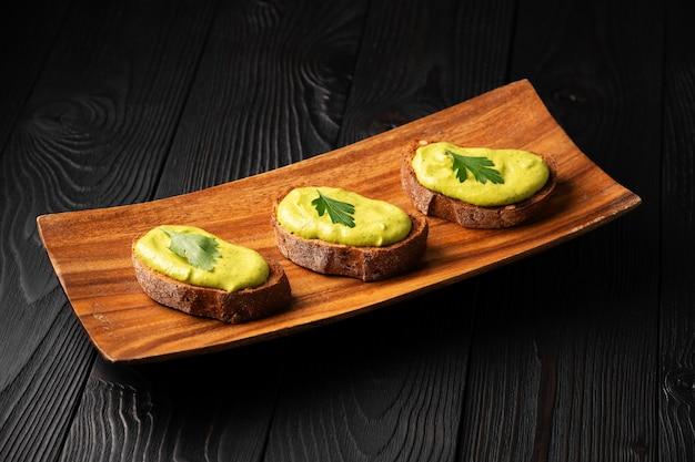 Sandwiches mit geröstetem brot und kürbiskaviar mit petersilie auf einem hölzernen hintergrund