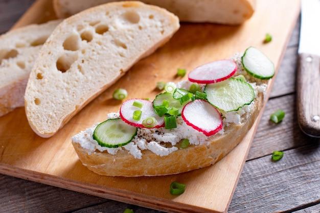 Sandwiches mit gurken, radieschen und frischkäse auf holzbrett, nahaufnahme, frühstück oder mittagessen konzept
