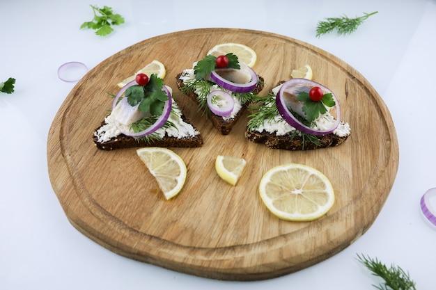 Sandwiches mit herings-zitronen-käse und zwiebeln auf holzbrett