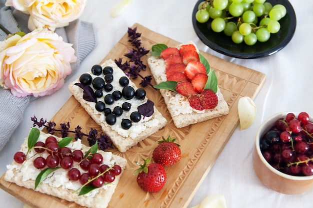 Sandwiches mit hüttenkäse und beeren an bord und blumen