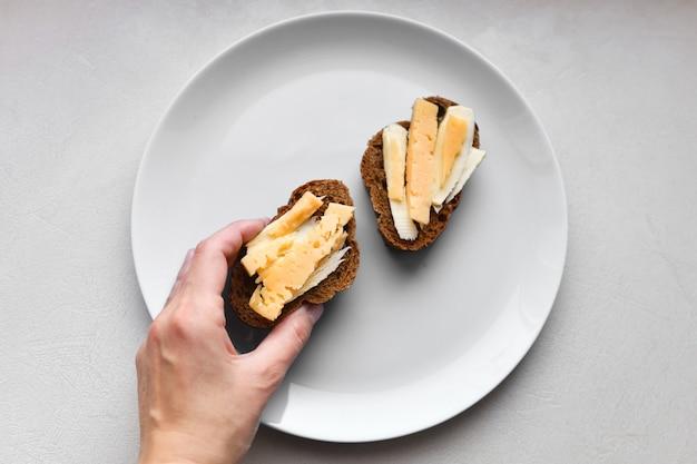 Sandwiches mit käse. zum frühstück. mehrfarbige platte. tafel. hausgemachtes frühstück. käsesandwich zum frühstück auf einem weißen tisch