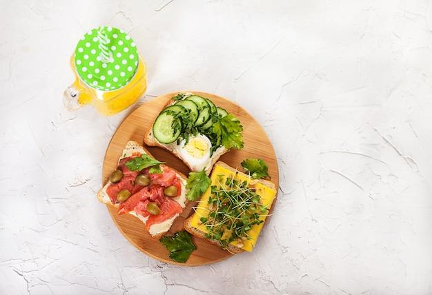 Sandwiches mit lachs, sprossen, tomaten, gurken, eiern und petersilie auf einem holzbrett