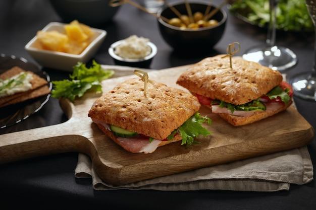 Sandwiches mit parma serviert auf schneidebrett und vorspeisen herum
