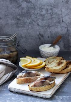 Sandwiches mit quark und gravlax aus makrele, serviert mit zitrone.